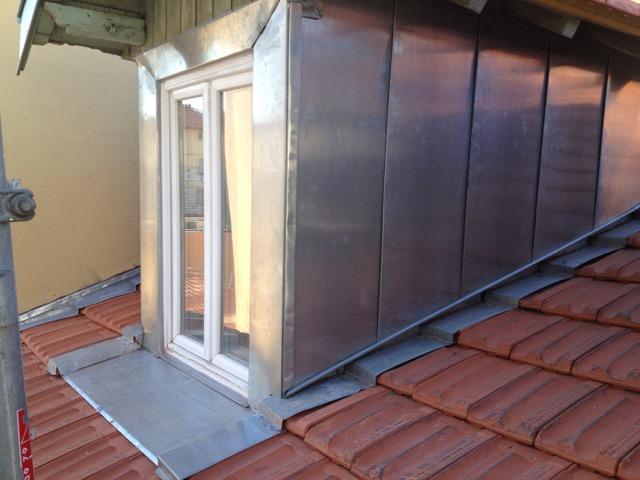 Structure de zinc autour d'une fenêtre dépassant d'un toit en tuiles plates
